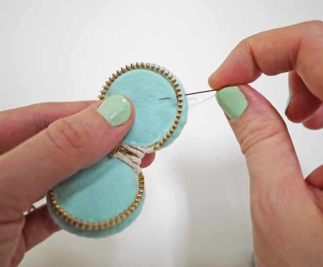 sewing the felt-covered button parts to the zipper on the macaron zipper pouch